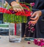 Blühen Sie das Vereinbaren des zeitgenössischen Brautblumenstraußes unter Verwendung des Bambusses und des Plastiks lizenzfreie stockbilder