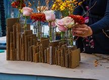 Blühen Sie das Vereinbaren von roten, gelben und rosa Blumen im cardbard und im Glas stockfotografie