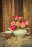 Blühen Sie in einem weißen Teetopf und in einer Weinlese, gemütlicher rustikaler Hauptdekor, Lizenzfreies Stockfoto