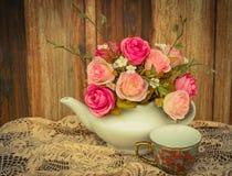 Blühen Sie in einem weißen Teetopf und in einer Weinlese, gemütlicher rustikaler Hauptdekor, Stockfotos