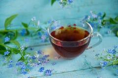 blühen Sie Tee und einen Blumenstrauß von Vergissmeinnichten auf einem hölzernen Hintergrund Stockbild