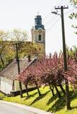 Blühende Kirschblüte-Bäume und alte Kirche, Saisonszene Stockfotos