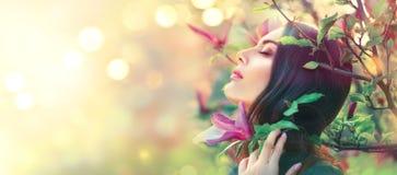 Blühende Magnolienbäume Berührenund riechende Frühlingsmagnolie der jungen Frau der Schönheit blüht lizenzfreie stockfotos