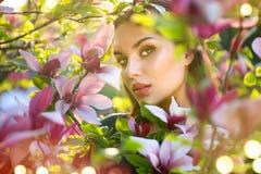 Blühende Magnolienbäume Berührenund riechende Frühlingsmagnolie der jungen Frau der Schönheit blüht Stockfotografie
