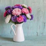 Blüht Astern in Weiß emailliertem Pitcher Stockbild