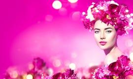 Blüht Frisur Schönheitsmodellmädchen mit rosa Pfingstrosenblumen winden über Purpur stockbild