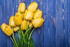Blüht gelben Blumenstrauß der Tulpen auf blauem backgraund Stockfotografie