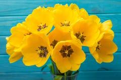 Blüht gelben Blumenstrauß der Tulpen auf blauem backgraund Lizenzfreie Stockfotografie