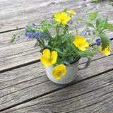 Blüht weißer Emailbecher der Weinlese mit kleinem Blumenstrauß von Butterblumeen Stockfotos