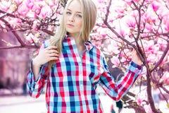 有看照相机的蓝眼睛的可爱的年轻金发碧眼的女人在bl附近 免版税库存图片
