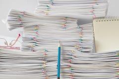Blå blyertspenna framme av högen av överbelastningsskrivbordsarbete Arkivfoton