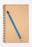 Blå blyertspenna på bruna anteckningsboks räkning. Arkivbild