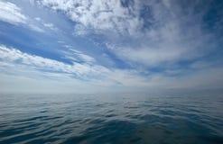 Blå himmel med moln över havet Arkivbild