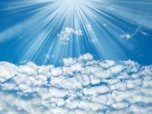 Blå himmel med solstrålar och moln Arkivbild