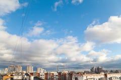 Blå himmel med vit fördunklar ovanför tak av lägenhethus Royaltyfri Bild