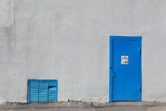 Blå metalldörr på den gråa stuckaturbyggnadsväggen Royaltyfri Foto