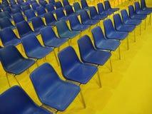 Bl?a stolar f?r breda rader f?r tomma platser p? gult golv arkivbild