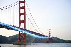 Blå strimma av ljusa förbigå Golden gate bridge mot klar himmel Royaltyfria Foton