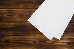Bl?tter des leeren Papiers auf h?lzernem Hintergrund stockfotos