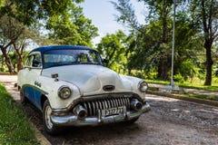 Blå vit klassisk bil som parkeras under träd i Kuba Arkivfoton
