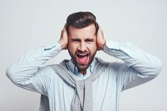 Bla bla bla! Young handsome man is stressed by noise, closing ears with both hands while standing on a grey background. Stress emotion stock photography
