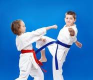 Blaast en blokkeert karate opleiden kinderen in karategi stock afbeelding