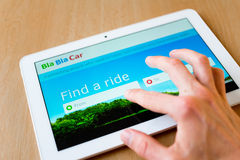 BlaBlaCar. Man's hand use with his fingers tablet. BlaBlaCar app is on the screen. BlaBlaCar is popular ridesharing social network that connects drivers and stock image