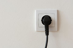 Black 220 volt power plug plugged in a socket Royalty Free Stock Photo
