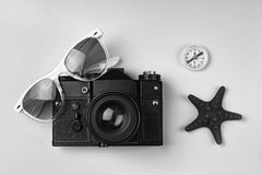Black abd white.The concept: travel, vacation, active leisure, sea voyages. Ancient camera, sunglasses, old compass and starfish o Stock Photo