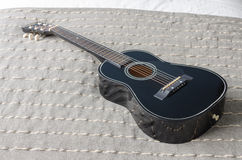 Black acoustic guitar on bed Stock Photography