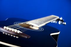 Black Acoustic Guitar On Blue Stock Image