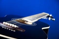 Black Acoustic Guitar On Blue Stock Image