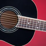 Black Acoustic Guitar On Red. A black acoustic guitar isolated against a red background in the square format with copy space Stock Image