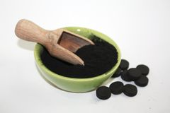 Black activated charcoal powder in a bowl with wooden utensil and few pills next. Photo stock photo