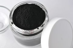 Black activated charcoal powder for detox facial mask. Black activated charcoal powder for detox face mask in a jar with copy space Stock Images