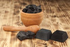Black activated charcoal soaps. Two hand made black soaps from activated carbon on a wooden plank stock images