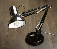 Black adjustable desk lamp on the wooden table Stock Images