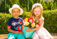 Black african american boy kid gives flowers to girl child on birthday. Little adorable children in park. Stock Photos