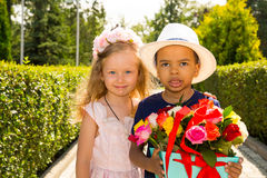 Black african american boy kid gives flowers to girl child on birthday. Little adorable children in park. Childhood and love. Royalty Free Stock Photography