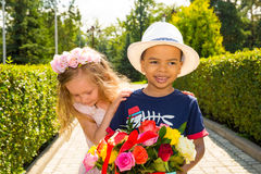 Black african american boy kid gives flowers to girl child on birthday. Little adorable children in park. Childhood and love. Royalty Free Stock Photos
