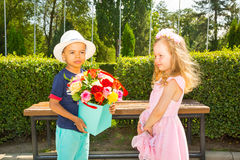 Black african american boy kid gives flowers to girl child on birthday. Little adorable children in park. Childhood and love. Stock Photos
