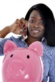 Black African American business woman putting coin into huge pink piggybank Royalty Free Stock Photo