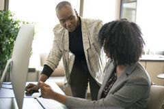 Black Female Businesswomen Coworkers or Job Training. Black African American businesswomen or coworkers together in an office doing teamwork or job training stock photography