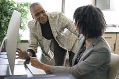 Black Female Businesswomen Coworkers or Job Training. Black African American businesswomen or coworkers together in an office doing teamwork or job training stock images