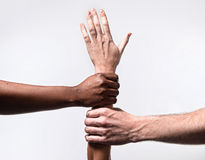Black African American and Caucasian hands holding together white skin arm in world unity Royalty Free Stock Photos