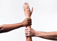 Black African American and Caucasian hands holding white skin arm in world unity Royalty Free Stock Photography