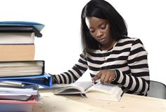 Black African American ethnicity student girl studying textbook. Young black African American ethnicity student girl studying pile of books on library desk Stock Photos