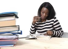 Black African American ethnicity student girl studying textbook. Young black African American ethnicity student girl studying pile of books on library desk stock image
