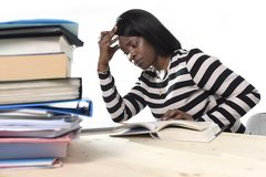 Black African American ethnicity student girl studying textbook. Young black African American ethnicity student girl studying pile of books on library desk Royalty Free Stock Images