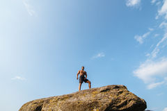 Black african american man bodybuilder posing on the rock with blue sky background Royalty Free Stock Images